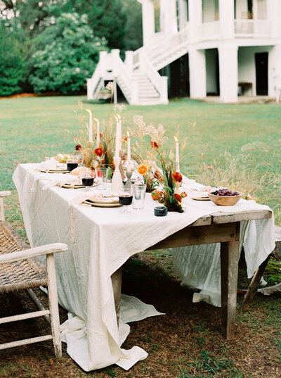 Farmhouse table with foraged flower arrangements, charcuterie and wine overflowing for a cozy fall wedding dinner