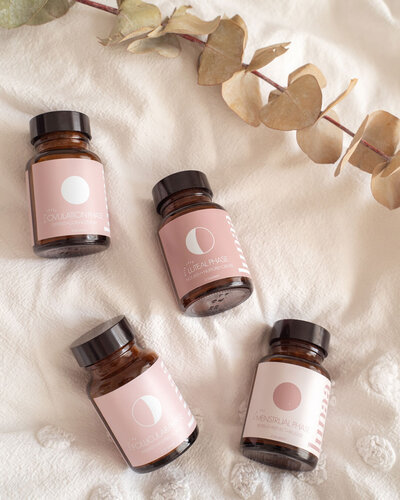 Lunaa Adaptogen organice blends that help with menstrual cycle and hormone balancing. Four amber glass jars laying on a bed with a dried eucalyptus branch.