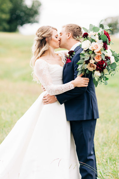 bride and groom embrace and kiss in a field