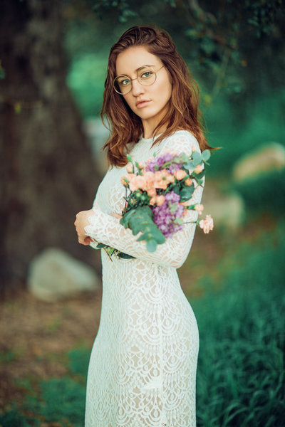 High-Fashion Wedding Editorial of Model in white wedding gown posing with handmade bouquet in a field