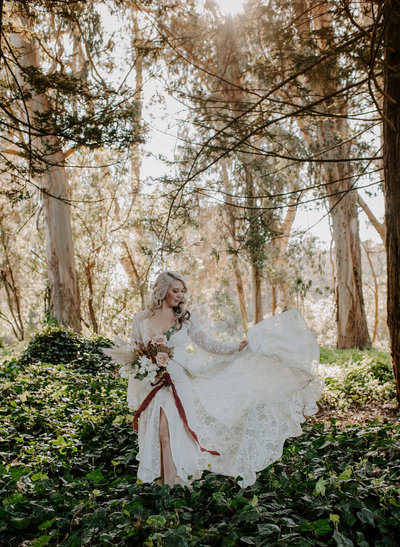 bride wearing wedding dress and holding bridal bouquet while standing in woods