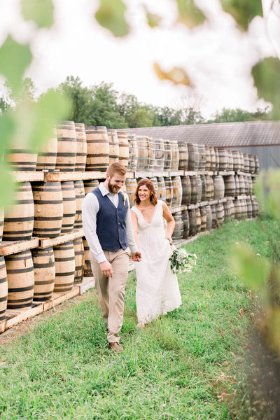 Burbon barrels and beautiful foreground frame this bride and groom on their wedding day at the Tuthilltown Spirits & DIstillary in Gardiner NY