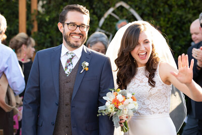 Bride and groom smile triumphantly and wave at guests while walking back down the aisle married