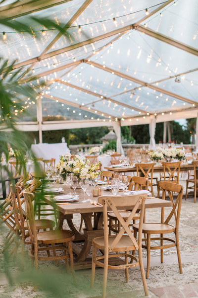 The stars shine down on this Miami wedding reception thanks to a clear top tent.  The long wooden tables are complimented by classy florals and high end gold flatware.
