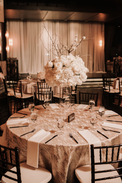 Textured centerpieces with white flowers on metallic print table linens
