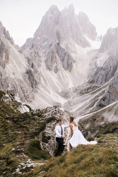 A groom helps his bride walk down a dirt hiking trail in the Dolomites. The bride wears a white dress with train and the mountain range rises behind them.