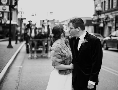 Bride and groom kissing in the street with horse drawn carriage in the background