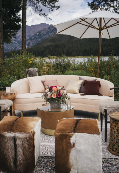 Reception seating area at dusk features a cream couch, circular coffee tables, and many cube fur stools