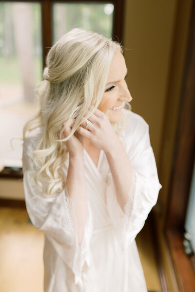 bride gets ready for her wedding day in her white robe, photo by Cynthia Boyle wedding photographer in michigan