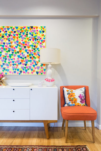 A modern white side table, colorful heart painting, and orange chair.