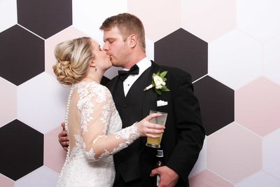 kissing couple front of a awesoem backdrop
