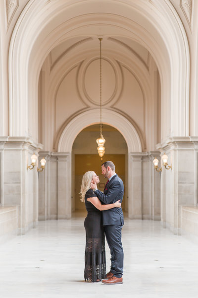 a couple share an intimate  moment during their san francisco city hall engagement session by Adrienne and Dani Photography