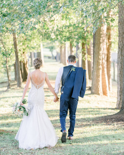 Bride and groom walking hand in hand at Yesterday Spaces wedding venue in Asheville NC - photo by Corey Johnson Studios NC Wedding Photographer
