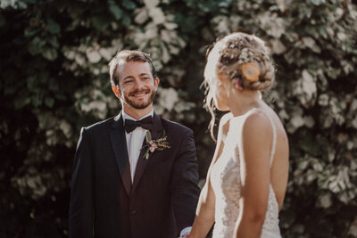 groom looking at his bride smiling while she walks in front of him and looks back