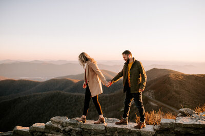 man and woman walking and holding hands with mountains in background