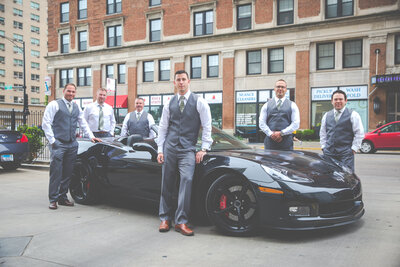 Groomsmen in gray tuxedos pose in front of a sport car in downtown Chicago.