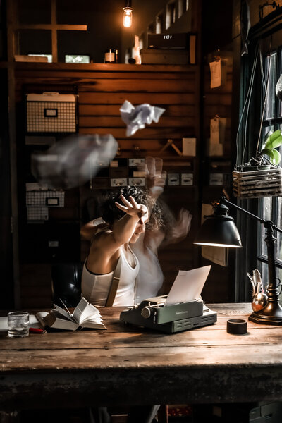 Image of Hannah Ellaham -BYOBrand Podcast host and Brand Expert Throwing Paper At Camera from Desk with Vintage Typewriter
