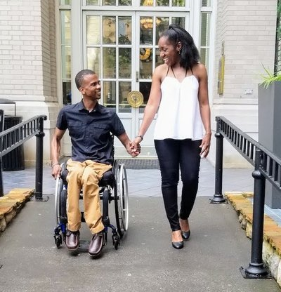 Melanie Grandoit and Ray Grandoit holding hands walking down the accessible ramp. Melanie and Ray became engaged in 2017.