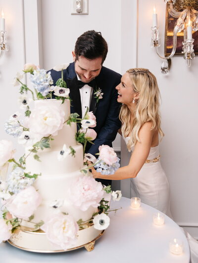Bride and groom laugh as they cut their wedding cake with wired flowers