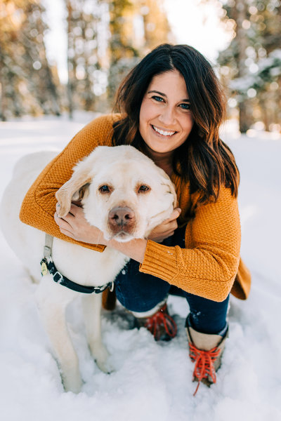 woman hugging dog while smiling