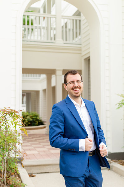 Tampa Florida wedding photographer poses with a smile in his blue suite and white dress shirt in a light and airy location