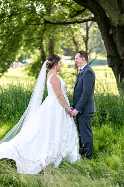 bride and groom standing in tall grass summer wedding