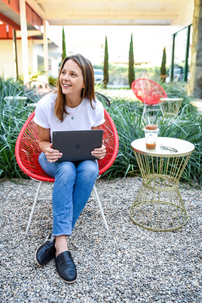 Portrait of brunette woman smiling while working on laptop in a red chair