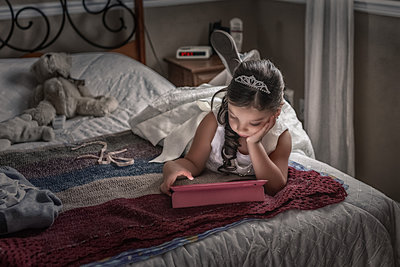 Flower Girl with iPad laying on bed in a Toronto Wedding. This beautiful flower girl is wearing a tiara and her flower girl dress while laying on a bed, playing with the iPad until her time is ready. A soft light pours on the flower girl from window right, and her arm props her head up like she's a little bored.