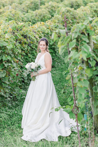Image of bride in a line white dress in vines. Photo captured by wedding photographer in Virginia.