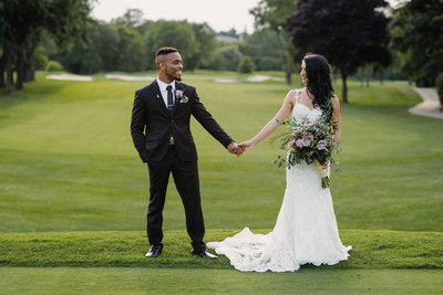 Couple holding hands on golf course in Toronto