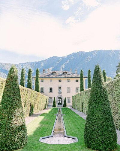 Villa Balbianello wedding venue in Lake Como with manicured lawns, cypress trees and a stately fountain