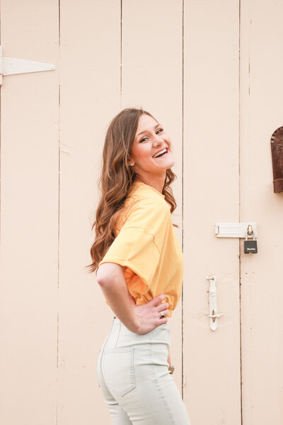 woman smiling outside standing against a barn door