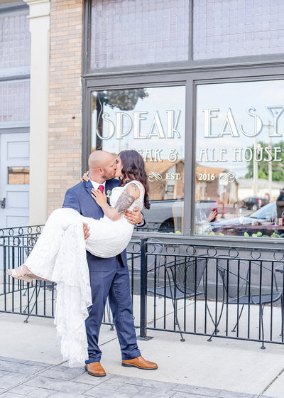 Bride and groom kiss outside speakeasy on their wedding day - Georgia wedding photographer