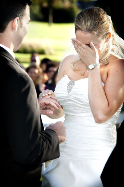 A bride cries while exchanging vows during an outdoor wedding ceremony.