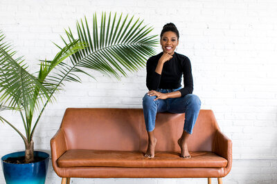 black woman with plants and couch