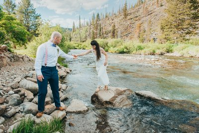 Couple crosses river on rocks in the Breckenridge mountains of Colorado for their adventure wedding