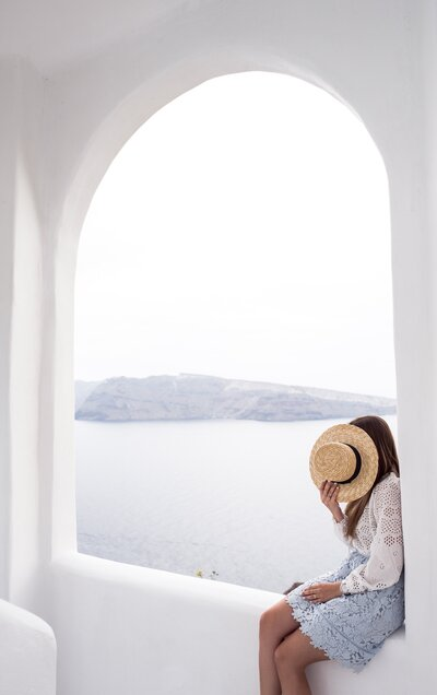 Girl covering her face with her hat in Santorini Greece