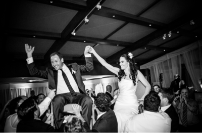 Bride and groom hold hands while being lifted in chairs at wedding reception