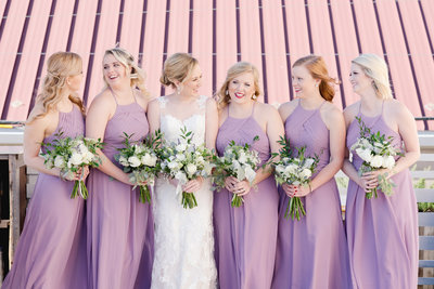 Bride and her bridesmaids in lavender smile and hold bouquets