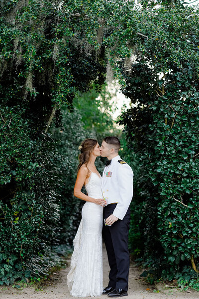 Garden allée at Middleton Place for a newlywed portrait spot where they share a sweet kiss