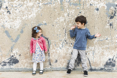 2 young kids standing in front of a wall