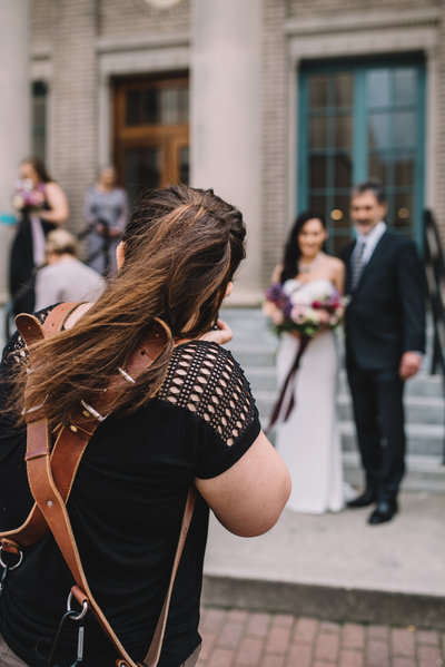 photographer taking picture of bride & groom