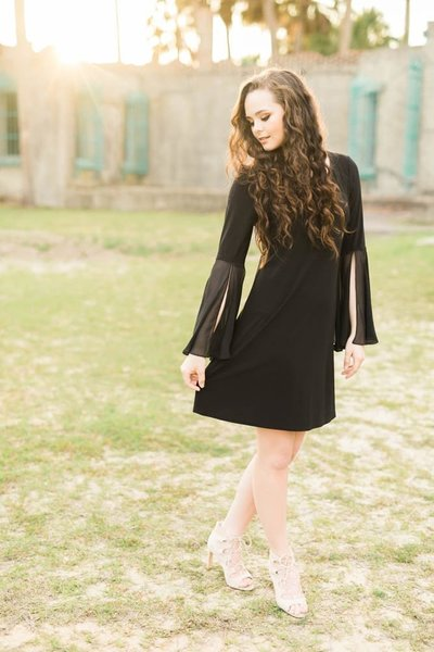 senior in black dress posing for portraits in Myrtle Beach