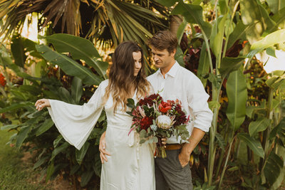 bride and groom standing in front of banana trees