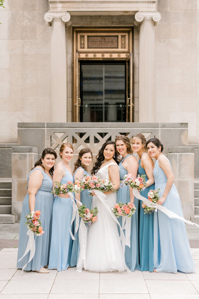 bride stands in the middle with her bridesmaids in dusty blue dresses surround her in the courtyard of the cincinnati art museum in cincinnati ohio bride and bridesmaid hold their flower bouquets by cincinnati wedding florist roots floral design