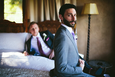Same sex couple poses for photo in their wedding suits