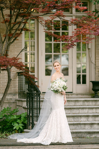 Bride holding white bouquet smiling in front of stairs at Dallas Arboretum Wedding