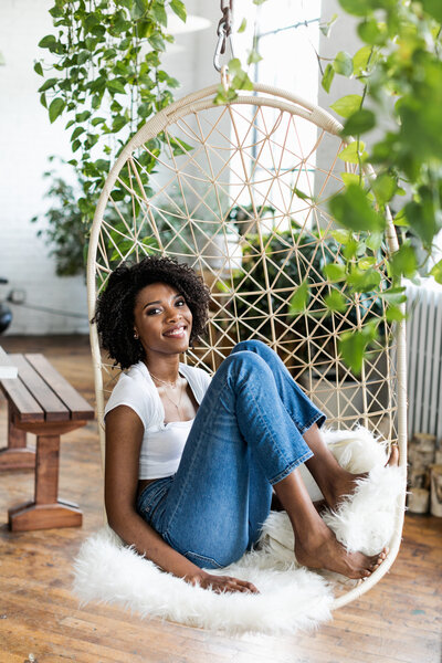 black woman with plants and swinging chair