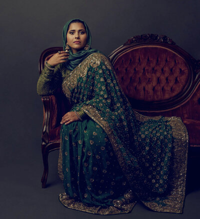 Fine art portrait of a woman in a green and gold sari sitting on an antique sofa. Houston, TX.