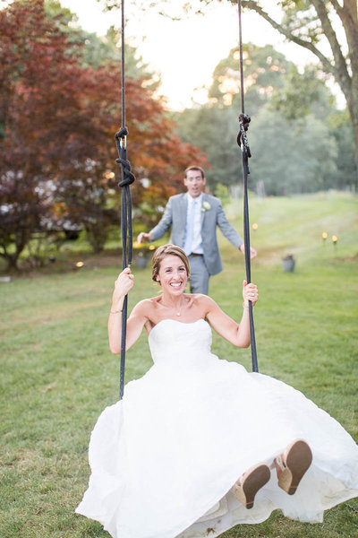 Bride gets a push from the groom on the tree swing